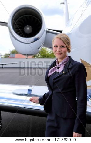 Young flight attendat standing by the wing of executive jet