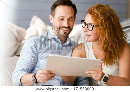 Happy to be in touch. Pleasant cheerful positive couple sitting at home and having conversation while expressing happiness and sharing opinions