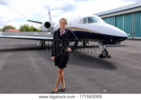 Stewardess standing in front of executive jet