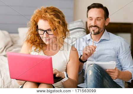 Getting acquainted with new gadget. Concentrated charming senior couple sitting at home and working while expressing positivity and using the laptop and taking notes