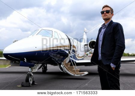 Young manager with hands in pockets and sunglasses by his aircraft