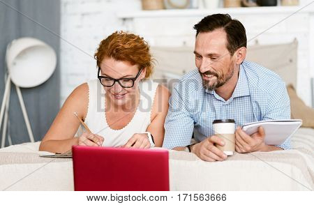 Full of creativity. Sociable smiling curious couple lying at home and using the laptop while expressing positive emotions and taking notes