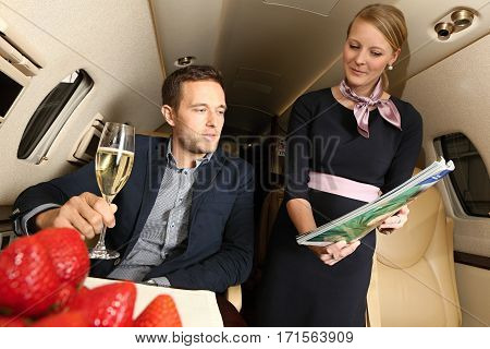 Young man holding glass of champagne choosing the magazines offered by airhostess