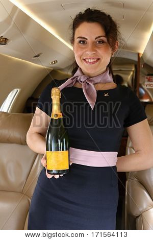 Airhostess standing in the cabin with the bottle of champagne