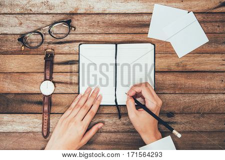 woman hands writting down on the book Top View on wooden table Top View with Copy Space on vintage background.