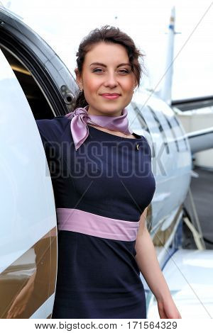 Brunette airhostess standing in the open door of mid-size jet