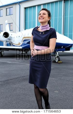 Brunette uniformed flight attendat laughing by the small jet plane
