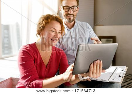 Useful family weekend. Cheerful inventive energetic middle aged couple sitting at home and using the tablet while expressing positivity and making notes