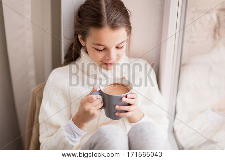 childhood and people concept - beautiful girl with cacao mug in sweater sitting at home window in winter