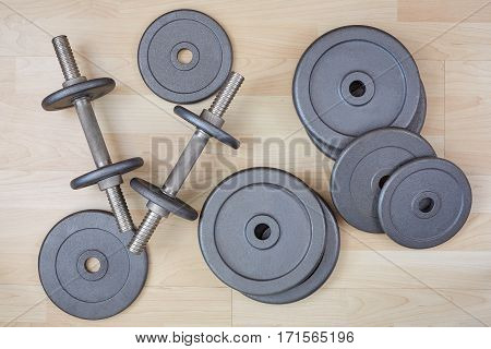 dumbbell and free weight on wooden floor