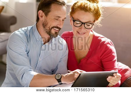 Full of delight. Optimistic energetic happy middle aged couple sitting at home and using the tablet while expressing positivity and making notes