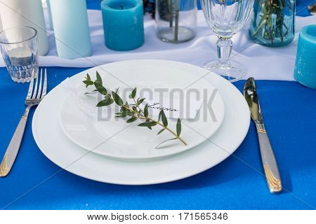 Plates with greenery. Table served with cutlery, stemware and candles on a blue tablecloth
