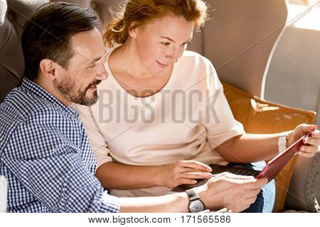 In love with you. Smiling involved cheerful middle aged couple sitting at home on the couch and using the laptop while expressing positivity and happiness