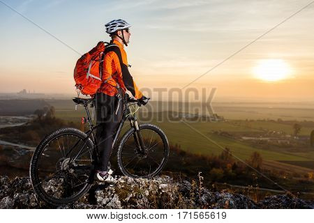 A cyclist with a backpack on a background of blue sky and the field. Cyclist in the orange jacket, helmet and sunglasses. Beautiful landscape with green field, sky, hill and rocks. Travel in the countryside. Spring season.