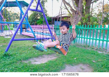 Sad Asian Boy Play A Iron Swinging At The Playground Under The Sunlight In Summer.