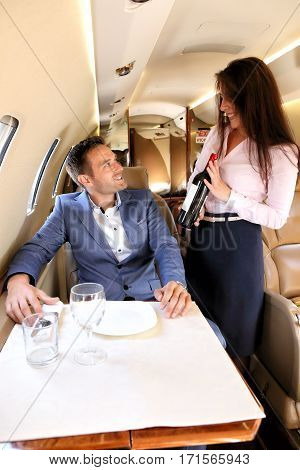 Stewardess offering the wine to young passenger of business jet