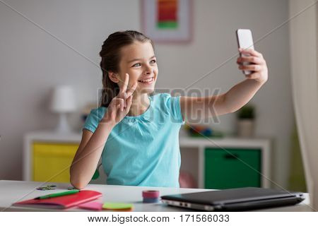 people, children and technology concept - girl with laptop computer and smartphone taking selfie or having video call at home