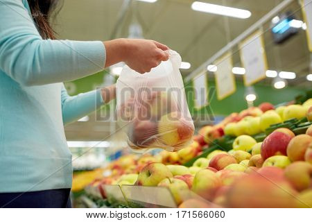 sale, shopping, food, consumerism and people concept - woman holding bag with apples at grocery store