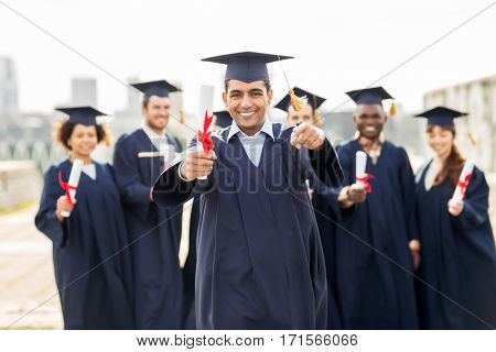 education, graduation and people concept - group of happy international students in mortar boards and bachelor gowns with diplomas pointing finger at you