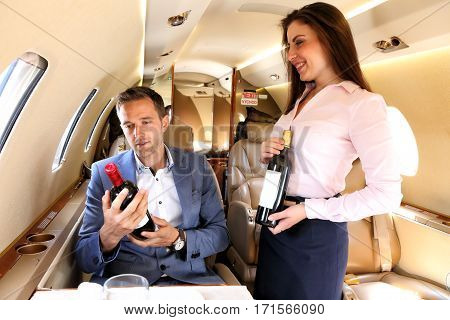 Passanger of executive jet considering the wine selection offered by airhostess