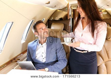 Business jet airhostess bringing the cup of coffee to the passenger