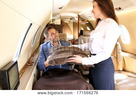 Stewardess handing a pillow to a blanket covered passanger of business jet