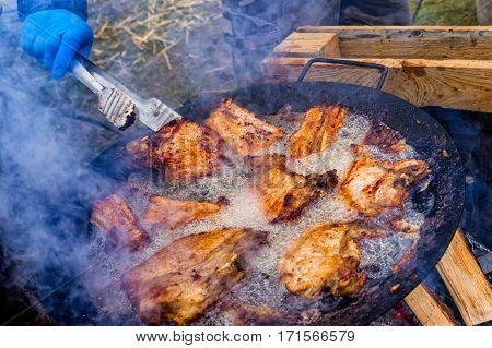 Hecha Ukraine - February 11 2017: Cook one of the teams of butchers fry the bacon in a frying pan during the 11th International gastronomic festival of butchers in the village Hecha.