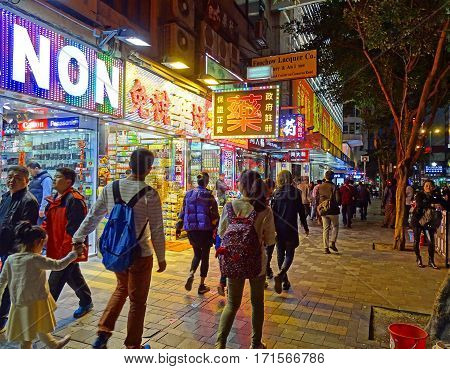Tsim Sha Tsui, Hong Kong - February 9, 2016: People stroll along the shops of Nathan Road towards Victoria Harbour.