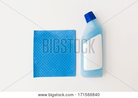 cleaning stuff, housework, housekeeping and household concept - bottle of detergent and blue rag on white background