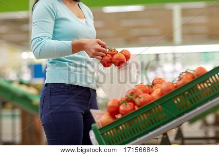 sale, shopping, food, consumerism and people concept - woman with bag buying tomatoes at grocery store