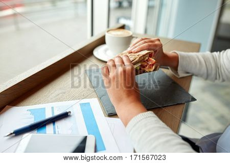 business, food and people concept - woman with papers eating salmon panini sandwich at cafe for dinner or lunch