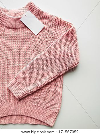 clothes, fashion and objects concept - close up of sweater or pullover with price tag on white background