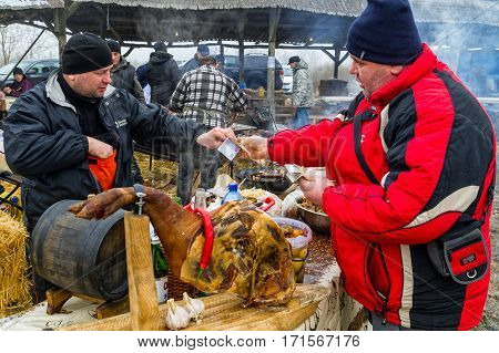 Hecha Ukraine - February 11 2017: Visitor (R) buys fresh smoked sausage from pork during the 11th International gastronomic festival of butchers in the village Hecha.