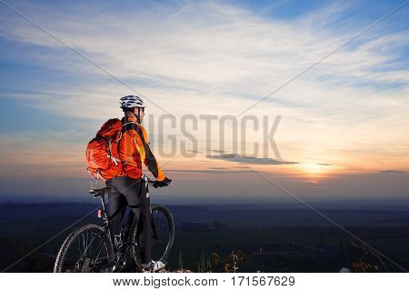 Sun rises behind man getting ready to ride his road bike on lonely paved highway during summer. Includes copy space. Man in orange jacket, helmet, black sunglasses and with red backpack. Background wiyh sunrise.