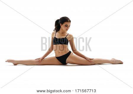 Sporty sexy brunette in black top and pants sitting gracefully in split studio portrait