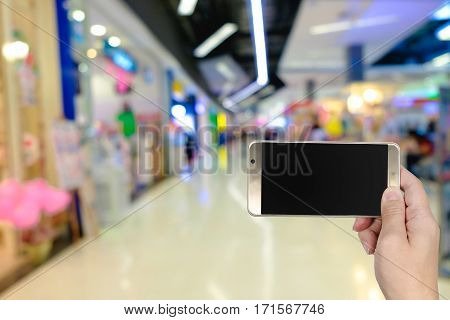 Right Hand Using Smart Phone With Blank Screen On Abstract Blur Background Of Storefront In Fashion