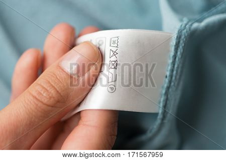 clothes, laundry, people and housekeeping concept - close up of hand holding label with users manual of clothing item