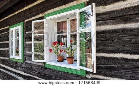 pair of wooden windows with green frame on the timbered wall