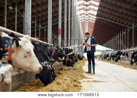 agriculture industry, farming, people and animal husbandry concept - happy young man or farmer with clipboard and cows in cowshed on dairy farm