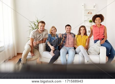 friendship, leisure, people and entertainment concept - happy friends with remote watching tv at home