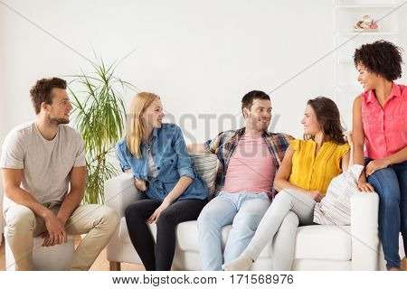 friendship, communication and people concept - group of happy friends talking at home