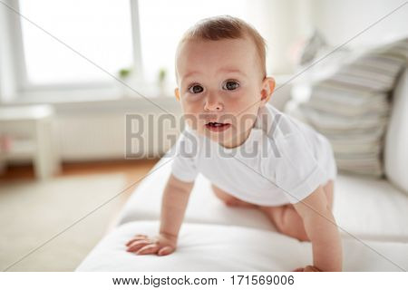 childhood, babyhood and people concept - little baby boy or girl crawling along sofa at home
