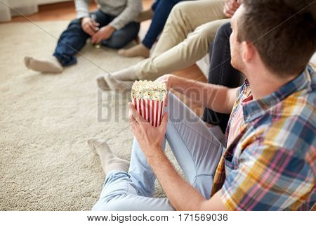 friendship, junk food and people concept - close up of man with friends eating popcorn at home