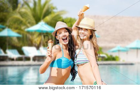 summer holidays, vacation, food, travel and people concept - smiling young women eating ice cream over swimming pool background