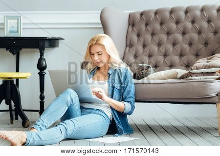 Work and enjoy. Young hardworking pretty woman using her laptop while spending time at home with her cat and relaxing.