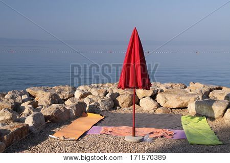 Closed red parasol by blankets on the stony beach