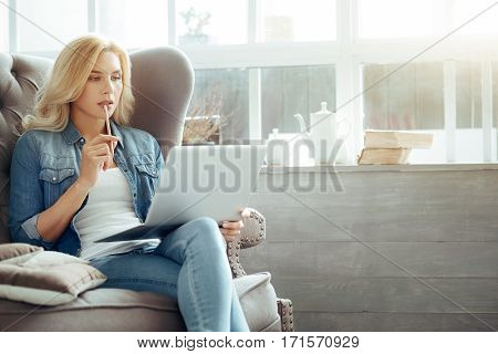 Work hard. Beautiful young concentrated woman sitting on sofa and using laptop while spending time at home.