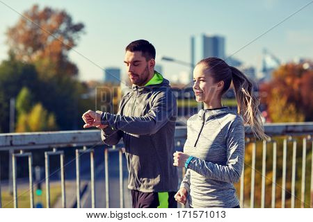 fitness, sport, people, technology and healthy lifestyle concept - smiling couple with heart-rate watch running over city highway bridge