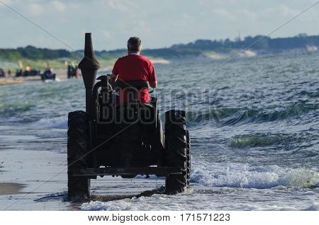 OLD TRACTOR - The restored old farm machine on the sea shore during the rally lovers