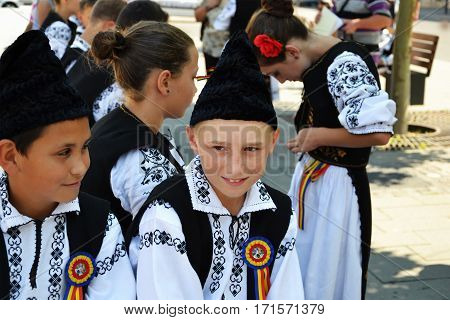 CLUJ-NAPOCA ROMANIA - AUGUST 04 2012: Group of young boys and girls dressed in traditional Romanian costumes rest in the shadow while waiting their turn to perform on an outdoor cultural event.